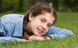 Retrato de la hembra joven mientras que miente en jardín del verde de la primavera Fotografía de archivo libre de regalías