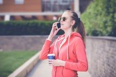Retrato de la hembra joven que hace una llamada usando smartphone y h Fotografía de archivo libre de regalías