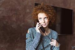 Retrato de la hembra joven rizada sonriente bonita del pelirrojo que usa el teléfono imagen de archivo