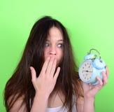 Retrato de la hembra joven soñolienta en el caos que sostiene el reloj contra g Fotos de archivo