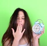 Retrato de la hembra joven soñolienta en el caos que sostiene el reloj contra g Imagen de archivo