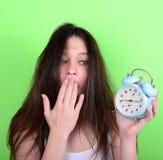 Retrato de la hembra joven soñolienta en el caos que sostiene el reloj contra g Fotografía de archivo