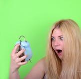Retrato de la hembra joven soñolienta en el caos que sostiene el reloj contra g Imagen de archivo libre de regalías