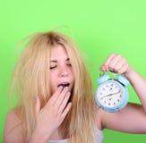Retrato de la hembra joven soñolienta en el caos que sostiene el reloj contra g Fotos de archivo libres de regalías