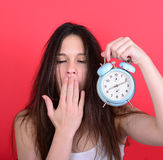 Retrato de la hembra joven soñolienta en el caos que sostiene el reloj contra r Fotos de archivo