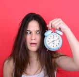 Retrato de la hembra joven soñolienta en el caos que sostiene el reloj contra r Imagen de archivo