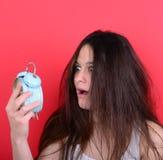 Retrato de la hembra joven soñolienta en el caos que sostiene el reloj contra r Fotografía de archivo