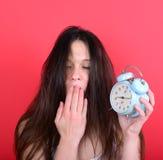 Retrato de la hembra joven soñolienta en el caos que sostiene el reloj contra r Imagen de archivo libre de regalías