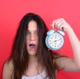 Retrato de la hembra joven soñolienta en el caos que sostiene el reloj contra r Foto de archivo