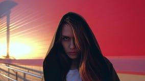 Retrato de la hembra mística asombrosa con el pelo largo, mirando adentro a la cámara con una mirada estricta en fondo rojo almacen de metraje de vídeo