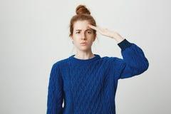 Retrato de la hembra seria atractiva con el pelo rojo y las pecas que se colocan en suéter azul del invierno que saluda con la pa Fotografía de archivo