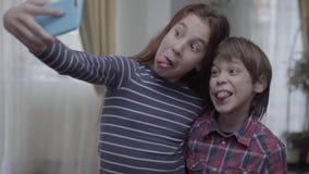 Retrato de la hermana y del hermano que hacen el selfie en casa metrajes