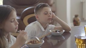 Retrato de la hermana y de su gemelo cansado del hermano que intentan comer las gachas de avena o los copos de maíz para el desay almacen de metraje de vídeo