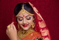 Retrato de la joyer?a del oro de la novia que lleva india joven y de la sari roja en la boda imágenes de archivo libres de regalías