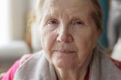 Retrato de la localización mayor de la mujer cerca de la ventana Foto de archivo libre de regalías