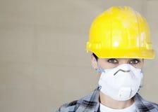 Retrato de la máscara de polvo del trabajador que lleva de sexo femenino y casco de protección sobre fondo coloreado fotos de archivo libres de regalías