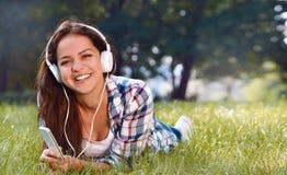 Retrato de la música que escucha de la chica joven bonita que miente en la hierba Fotografía de archivo libre de regalías