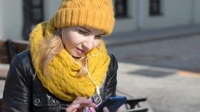 Retrato de la música que escucha de la chica joven con los auriculares usando el teléfono elegante en calle de la ciudad almacen de metraje de vídeo