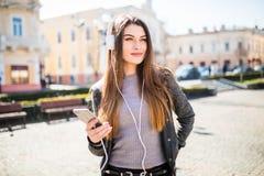 Retrato de la música que escucha de la muchacha feliz en línea con los auriculares inalámbricos de un smartphone en la calle en d Imagen de archivo