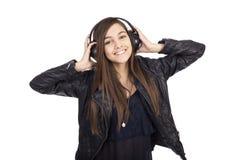 Retrato de la música que escucha de la muchacha linda feliz en sus auriculares Foto de archivo