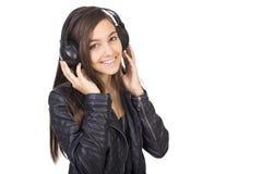 Retrato de la música que escucha del adolescente lindo en sus auriculares Fotografía de archivo