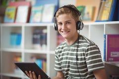 Retrato de la música que escucha del colegial feliz mientras que usa la tableta digital en biblioteca Fotos de archivo libres de regalías