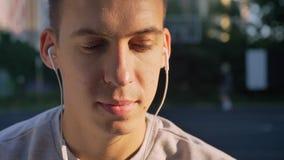 Retrato de la música que escucha hermosa del hombre joven a través de los auriculares y de mirar la cámara, gente que juega en fo almacen de metraje de vídeo