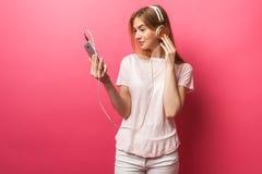 Retrato de la música que escucha de la muchacha feliz alegre en los auriculares que muestran la pantalla en blanco del teléfono m fotografía de archivo