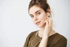 Retrato de la música que escucha sonriente de la muchacha hermosa joven en los auriculares que miran la cámara sobre el fondo bla Fotografía de archivo