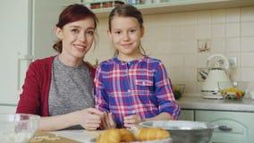 Retrato de la madre alegre y de la hija sonriente linda que miran la cámara mientras que cocina en la cocina el fin de semana Fam almacen de metraje de vídeo
