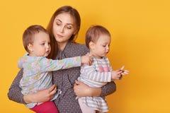 Retrato de la madre atenta responsable que pasa tiempo con sus pequeños niños, deteniendo a muchachas gemelas en los brazos, es fotografía de archivo libre de regalías