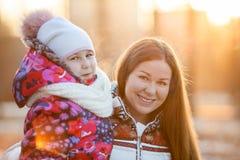 Retrato de la madre caucásica con el niño en el invierno, una tarde escarchada, sol, puesta del sol Fotografía de archivo libre de regalías