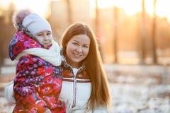 Retrato de la madre caucásica con el niño, una tarde escarchada, sol, puesta del sol Imagenes de archivo