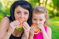 Retrato de la madre con su hija con las hamburguesas Imagen de archivo
