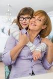 Retrato de la madre de abarcamiento de la hija cariñosa en casa Imagen de archivo