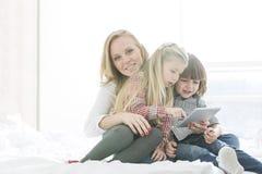 Retrato de la madre feliz con los niños que usan la tableta digital en dormitorio Fotos de archivo