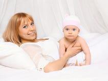 Retrato de la madre feliz que miente con el bebé junto en la cama Fotos de archivo