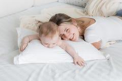 Retrato de la madre feliz que miente en la almohada grande con sus 9 meses de o Fotografía de archivo