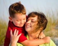 Retrato de la madre feliz y del hijo que abrazan en la playa Foto de archivo libre de regalías