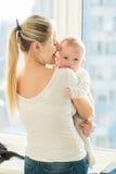 Retrato de la madre hermosa que abraza sus 3 meses del bebé en Foto de archivo