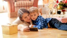 Retrato de la madre joven hermosa que miente en piso con su hijo del niño e historietas de observación en smartphone foto de archivo libre de regalías