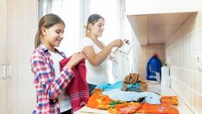 Retrato de la madre joven sonriente con ropa plegable de la hija adolescente después del lavadero Fotos de archivo