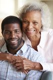 Retrato de la madre mayor sonriente que abraza al hijo adulto en casa fotografía de archivo