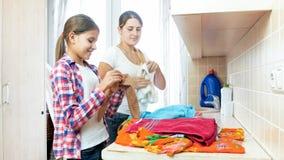 Retrato de la madre sonriente con el adolescente que clasifica la ropa en lavadero Imágenes de archivo libres de regalías