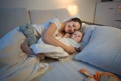 Retrato de la madre sonriente feliz que abraza y que miente con sus 9 meses del hijo del bebé en la noche Imagenes de archivo