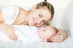 Retrato de la madre sonriente que miente con 3 meses del bebé en cama Fotos de archivo
