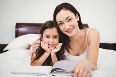 Retrato de la madre y de la hija con el libro en cama en casa Foto de archivo