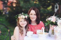 Retrato de la madre y de la hija en la tabla de té foto de archivo libre de regalías