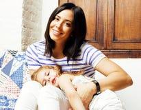 Retrato de la madre y de la hija jovenes sonrientes en casa, fam feliz Foto de archivo