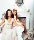 Retrato de la madre y de la hija jovenes sonrientes en casa, fam feliz Imágenes de archivo libres de regalías